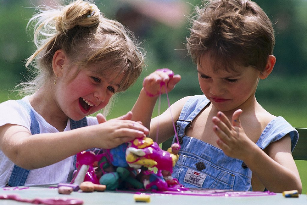 Boy, girls, plays, cheerfully, outside, summer, children, childhood, brother, sister, siblings, friends, Plastilin, game, together, does handicrafts, creative, creativity, happiness, fun, activity, casual activity : Stock Photo