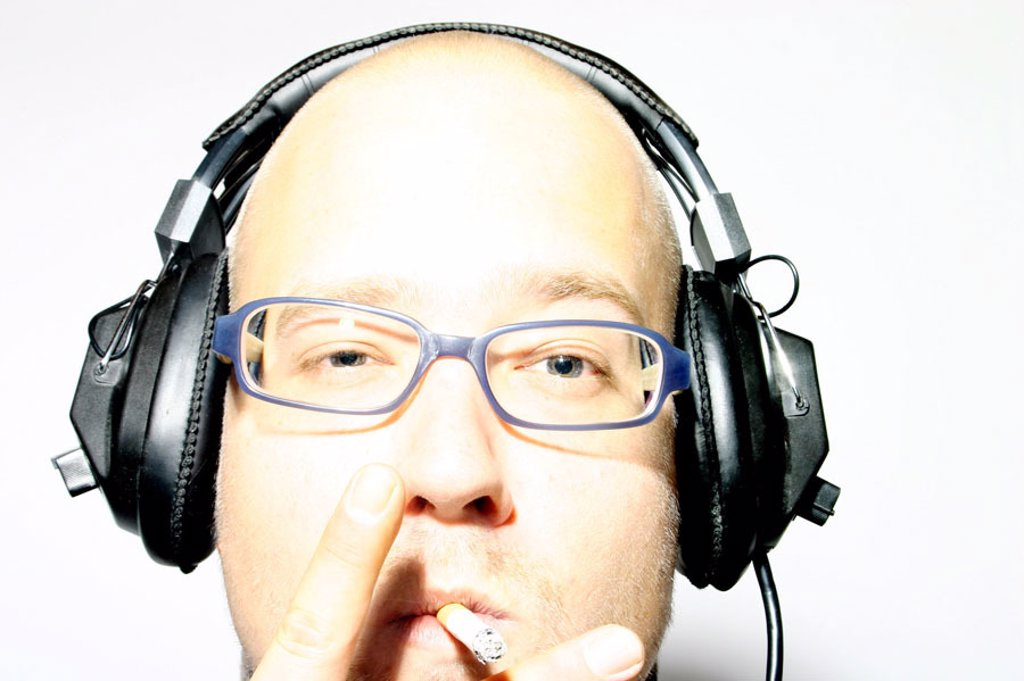 Man, young, bald head, headphones, cigarette, Portrait  Discjockey, disk jockey, DJ, musicians, type, 20-30 years, 30-35 years, head, face, truncated, bald-headed, bald, baldy, glasses, glasses bearers, , relaxen, enjoying, relaxing, alertly, interesting, : Stock Photo