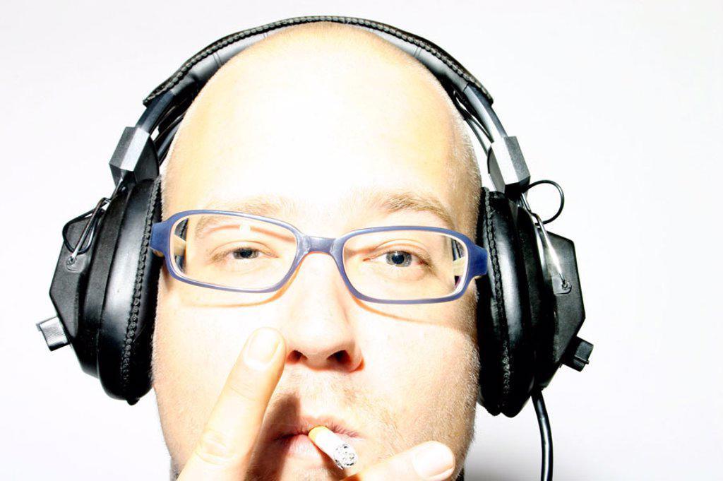 Stock Photo: 1558-60159 Man, young, bald head, headphones, cigarette, Portrait  Discjockey, disk jockey, DJ, musicians, type, 20-30 years, 30-35 years, head, face, truncated, bald-headed, bald, baldy, glasses, glasses bearers, , relaxen, enjoying, relaxing, alertly, interesting,