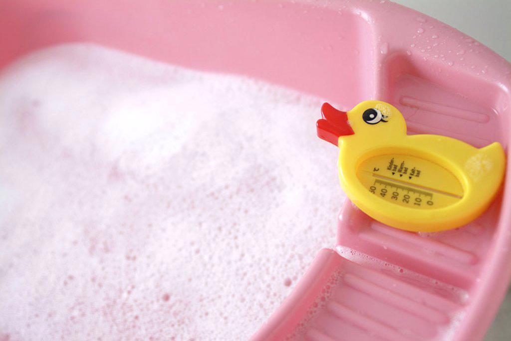 Stock Photo: 1558-60447 Baby bathtub, Seifenablage,  Detail, thermometers, duck form  Series, bathtub, baby tub, plastic tub, pink, water, bath water, foam, bath foam, bubble bath, temperature, water temperature, measures control, scale child bath warm bath cold bath animal form