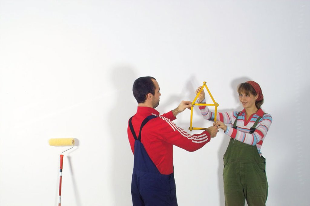 Do-it-yourself, couple, meter rod, holding,  Symbol, house, color scooters  Do-it-yourselfers, do-it-yourselfer, 20-30 years, working clothes, overalls, home works, renovation performances, renovates, renovation, independently, talent change craftspersons : Stock Photo