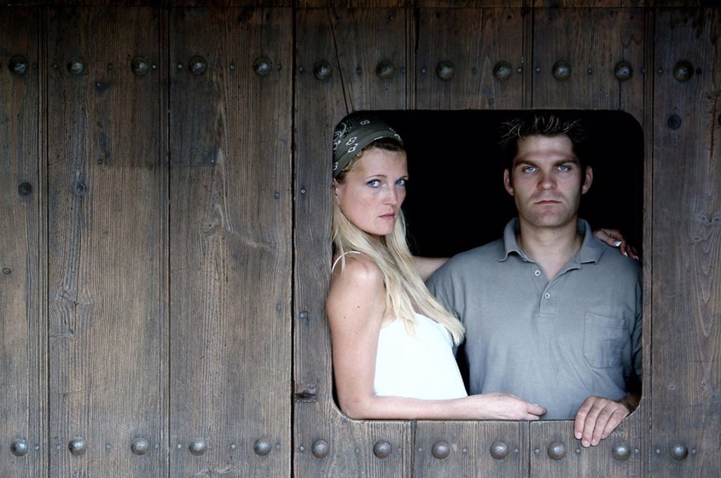 Stock Photo: 1558-64370 couple, young, Holzwand,  Window excerpt  Wall, wood, wood door, excerpt, windows, insight, view, 20-30 years, arm in arm, seriously, gaze camera, feeling, love, proximity, hiding place, secrecy,