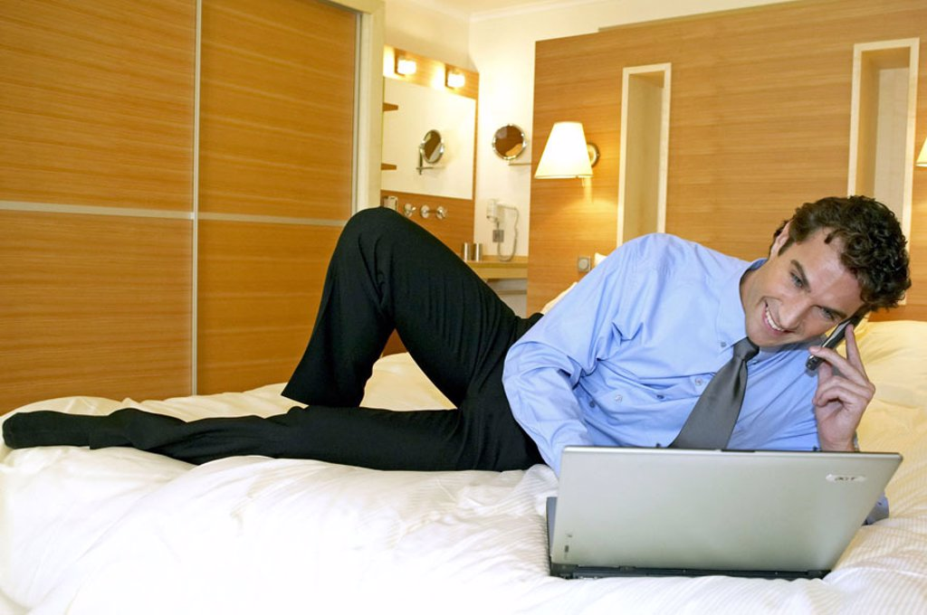 Hotel rooms, man, bed, lie,  Laptop, cell phone, smiling  Series, 30-40 years, businessman, portable phone,  Telecommunication, communication, computers wearable, Data input, information, data retrieval, work,  Contentment, balance, Workaholic, vacation, : Stock Photo