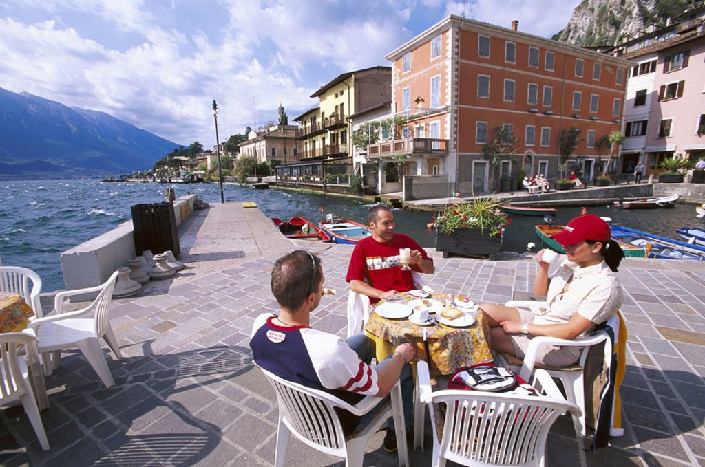 Stock Photo: 1558-67499 Italy, Trentino, Lake Garda, lime, Harbor, street cafe, guests  Men, woman, tourists, 30-40 years, boats, pub, cafe, people, tourism, gastronomy, coffee drinks, eat, snack, sunny, friends, enjoying conversation, vacation Feizeit travel time recuperation r