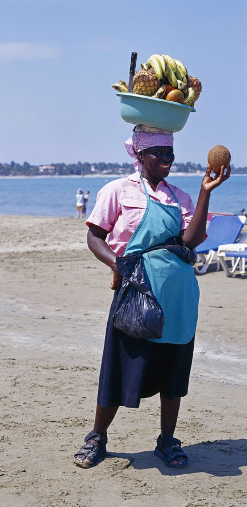 Stock Photo: 1558-68602 Dominican republic, Canakedte,  Beach, Obstverkäuferin, no models release! Caribbean, big Antilles, island, destination, tourism, woman, people of color, sales associate, bowl, fruit, differently, head, balances, coconut, holding, smiling, kindly, whole b