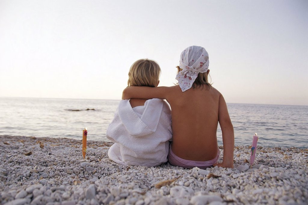 sitting beach, children, arm in arm,  view from behind  Girls, blond, two, 3 years, 7 years, bathrobe, kerchief, trunks, vacation, vacation, summer, evening, summer evening, sea gaze, outlook, wanderlust, homesickness, romanticism, torches, dusk, : Stock Photo