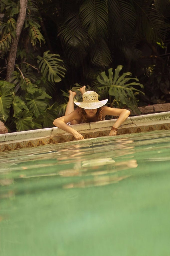 Stock Photo: 1558-69720 lie woman, straw hat, Poolwand,  Hands, water, cooling  20-30 years, 30-40 years, sunhat, headgear,  Hat, prone position, basin edge, pool, Swimmingpool, plantschen, refreshment, relaxation, recuperation, relaxen, enjoying, resting, well feeling, loneline