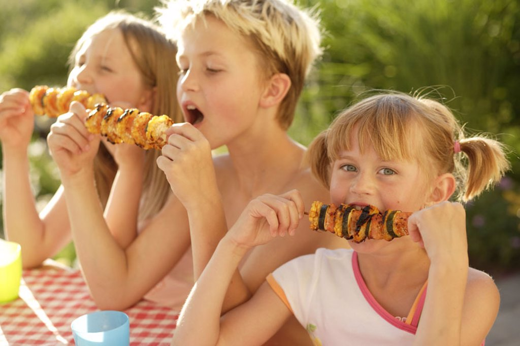 Children, garden, crickets, vegetable skewers,,  eats  Girls, boy, friends, siblings, three, table, sits, vegetables, skewers, foods nutrition healthy, vegetarian, bites off, enjoys, enjoyments, barbecue, leisure time, vacation, weekend, hunger, summers, : Stock Photo