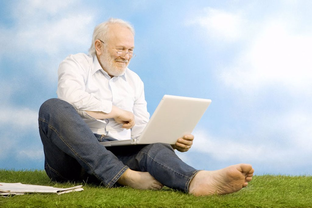 sitting senior, glasses, laptop, meadow,  smiling, joy  Series, man, 60-70 years, grey-haired, white-haired, beard, jeans, nakedfoot, ages, seniors, leisure time, vacation, recuperation, relaxation, Auszeit, pensionable ages, casual, modern, unlocked, int : Stock Photo