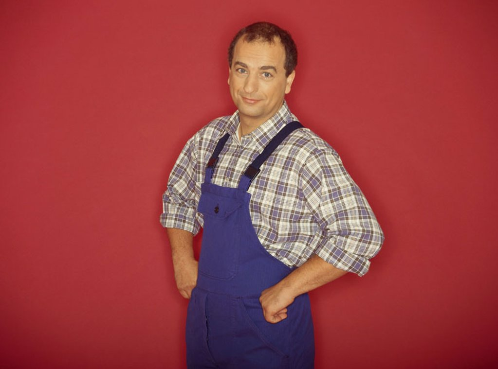 Stock Photo: 1558-75587 Man, middle age, overalls,  Hands, hips, eingestützt, Halbporträt  Series, men´s portrait, 40-50 years, dark-haired, shirt, checkered, jeans, workers, craftspersons, smiling, sympathetically, engages, studio, background red