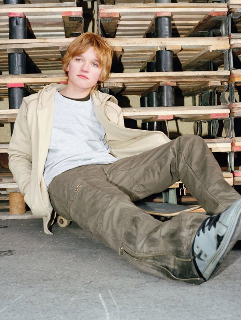 Stock Photo: 1558-75702 Teenager, skateboard, sitting,  Palette stack, leans  boy, youth, teenagers, 13-15 years, dreamy, gaze on the side, seriously, clothing, cool, nonchalant, casual, ´Schlabberlook´, bored, leans, waiting, loiters, ´zero buck generation´, Skater