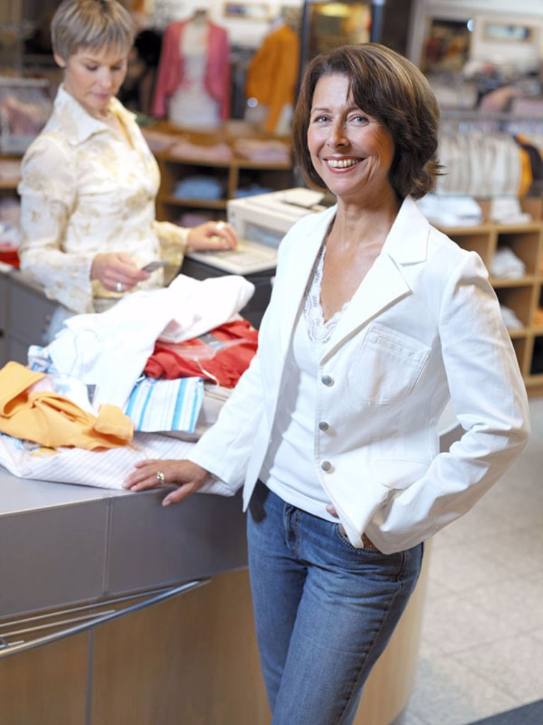 Department store, cash register, employees, customer,  middle age, smiling  Business, counter, bar, women, 40-50 years, well Age, kindly, cheerfully, sympathetically, been in the habit of, occupation, sales associate, scanners, price marks, sale, reading : Stock Photo