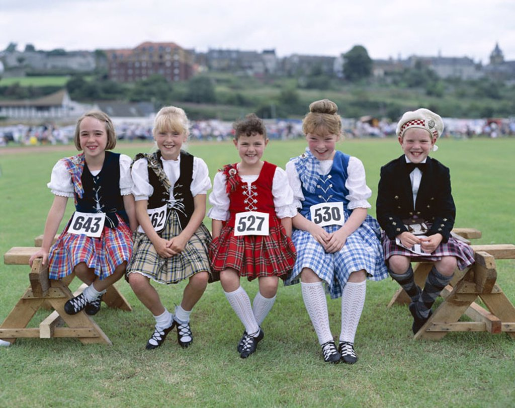 Stock Photo: 1558-79408 Scotland, Highland Games,  Highland Dancing, participants,  Girls, bank, sit, waiting  Europe, Great Britain, island, north, Highlands, party, event, culture, tradition, children, chorus, kilt, kilt, numbers, participant numbers, competition, pause, smili