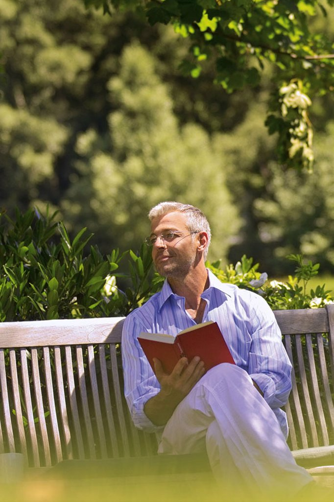 Stock Photo: 1558-80989 Garden bank, man, middle age, glasses,  sitting, dreamy, book, holding  Series, 40-50 years, well Age, glasses bearers grey-haired, short-haired, good-looking leisurewear leisure time recuperation, relaxation, hobby, reading, novel, reading, dreaming, tho