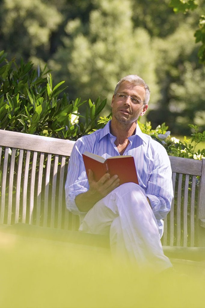 Garden bank, man, middle age, glasses,  sitting, dreamy, book, holding  Series, 40-50 years, well Age, glasses bearers grey-haired, short-haired, good-looking leisurewear leisure time recuperation, relaxation, hobby, reading, novel, reading, dreaming, tho : Stock Photo