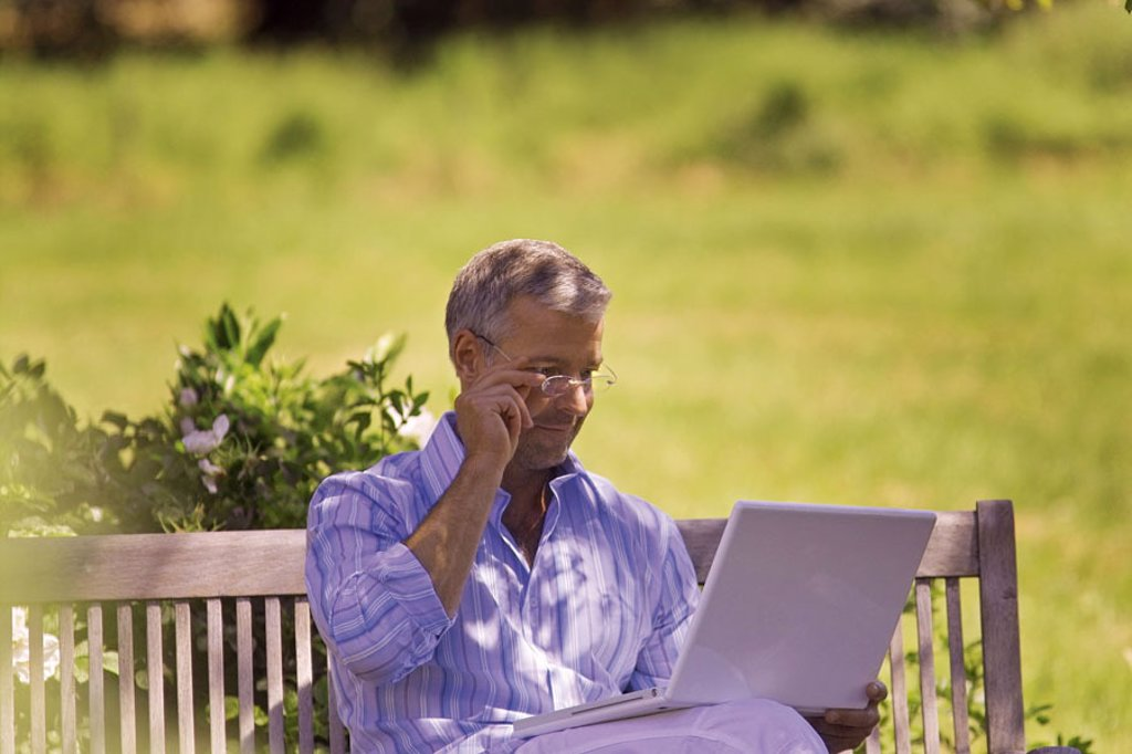 Stock Photo: 1558-80993 Garden bank, man, middle age, glasses,  sitting, laptop, reading  Series, 40-50 years, well Age, glasses bearers gesture grey-haired, short-haired, good-looking, leisurewear, leisure time, recuperation, relaxation, hobby, computers, wearable, e-mail, chat