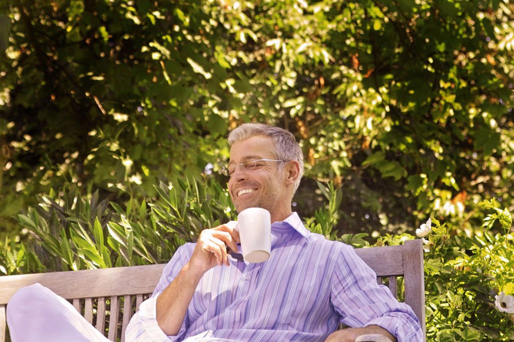 Garden bank, man, middle age, glasses,  smiling, coffee cup, holding  Series, 40-50 years, well Age, glasses bearers grey-haired, short-haired, good-looking leisurewear leisure time recuperation, relaxation, coffee pause, enjoying garden, bench wood bank : Stock Photo