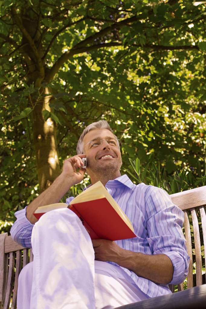 Garden bank, man, middle age, glasses,  sitting, cell phone, telephones, smiling,  Book, holding Series, 40-50 years, well Age, glasses bearers grey-haired, short-haired, good-looking leisurewear leisure time recuperation, relaxation, hobby, reading, nove : Stock Photo