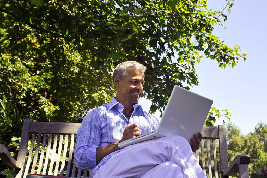 Stock Photo: 1558-81046 Garden bank, man, middle age,  sitting, laptop, data input   Series, 40-50 years, well Age, grey-haired, short-haired, good-looking, leisure time, hobby, computers, wearable, e-mail, smiling writes, reading, chatten, communication, telecommunication, User