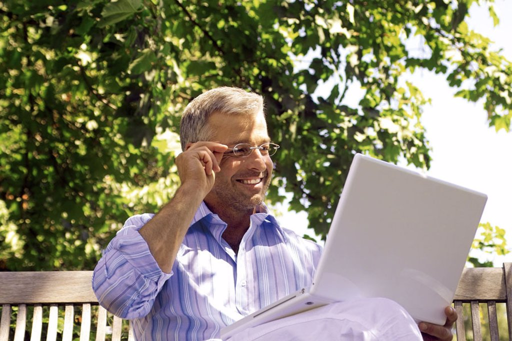 Garden bank, man, middle age, gesture,  Glasses, sitting, laptop  Series, 40-50 years, well Age, glasses bearers grey-haired, short-haired, good-looking leisurewear leisure time hobby, computers, wearable, smiling, e-mail, writes, reading, chatten, commun : Stock Photo
