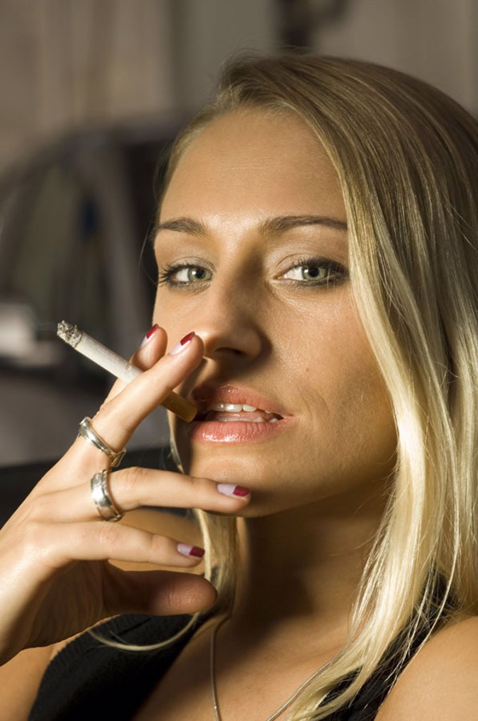 Stock Photo: 1558-81655 Woman, young, blond, cigarette,  smokes, gaze camera, portrait,   Series, 20-30 years, long hair, sitting, smoker, passenger seat, cool, carelessly, self-confidently, been in the habit of beautifully, makeup, radiation, jewelry, hand, fingers, rings, silv