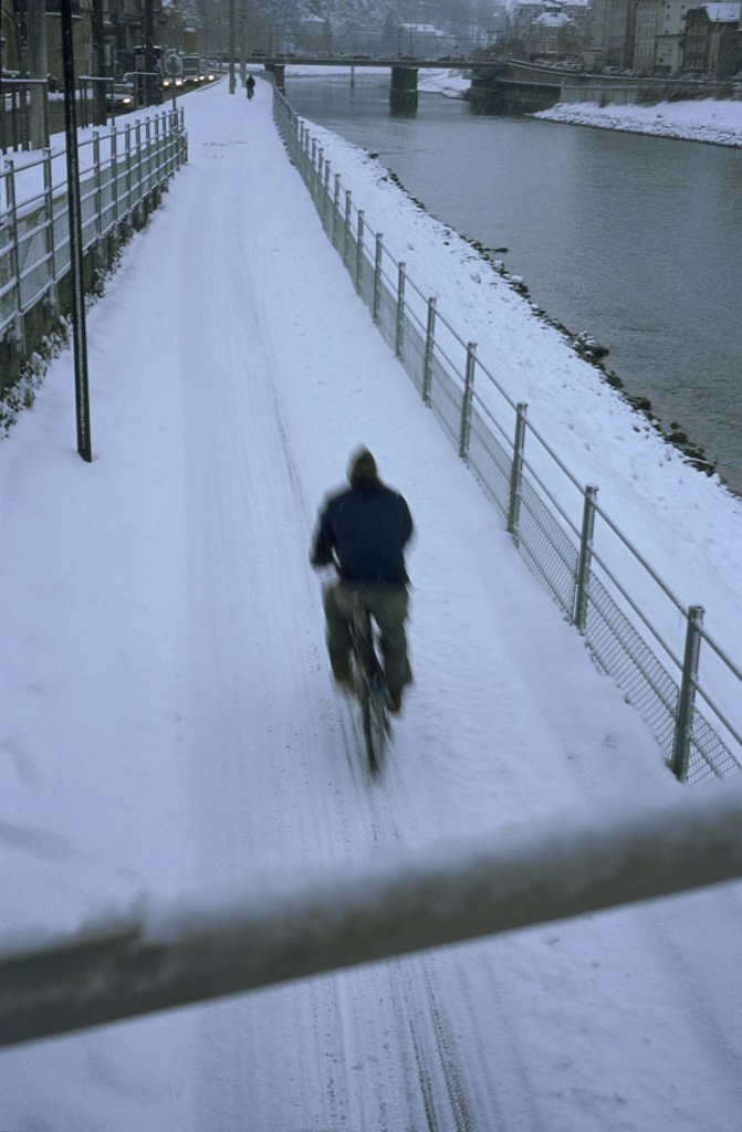Stock Photo: 1558-84707 Austria, Salzburg, Radweg,  snow-covered, bicyclists,  view from behind, twilight,  Bicycle way, cyclists, way, tracks, ungeräumt, snow, season, winters, twilight, riversides,