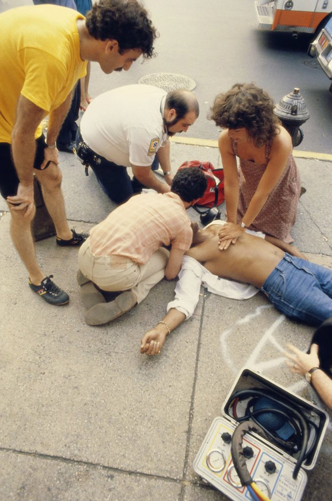 Stock Photo: 1558-86979 Roadside, sidewalk, victims, First helpers, reanimation,  no models release,  Man, casualties, patient, cardiac arrest, passer-bys, doctor on emergency call, doctor, first aid, Wiederbelebungsversuch,  Revival, emergency measures, emergency, accident,  Me