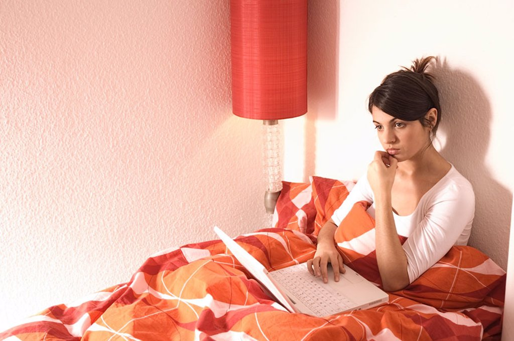 Woman, young, bed, sitting, laptop, thoughtfully, sad,   20-30 years, dark-haired, computer wearable, , thinking, loneliness, sorrow, worries, depressed, lovesickness, Mailen, Chatten, Internetsurfen, internet, telecommunication, mood negatively, cottage : Stock Photo