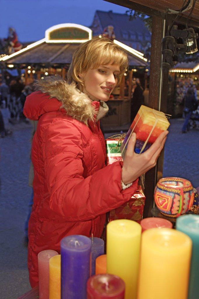 Christmas market, market stand,  Woman, candles, twilight, chooses,   30-40 years, blond, gift, Christmas articles, decoration objects, lights, wax candles,  colorfully, colored, pussy, looking at, selects, contemplating, shops, christmassy, Lifestyle, ev : Stock Photo