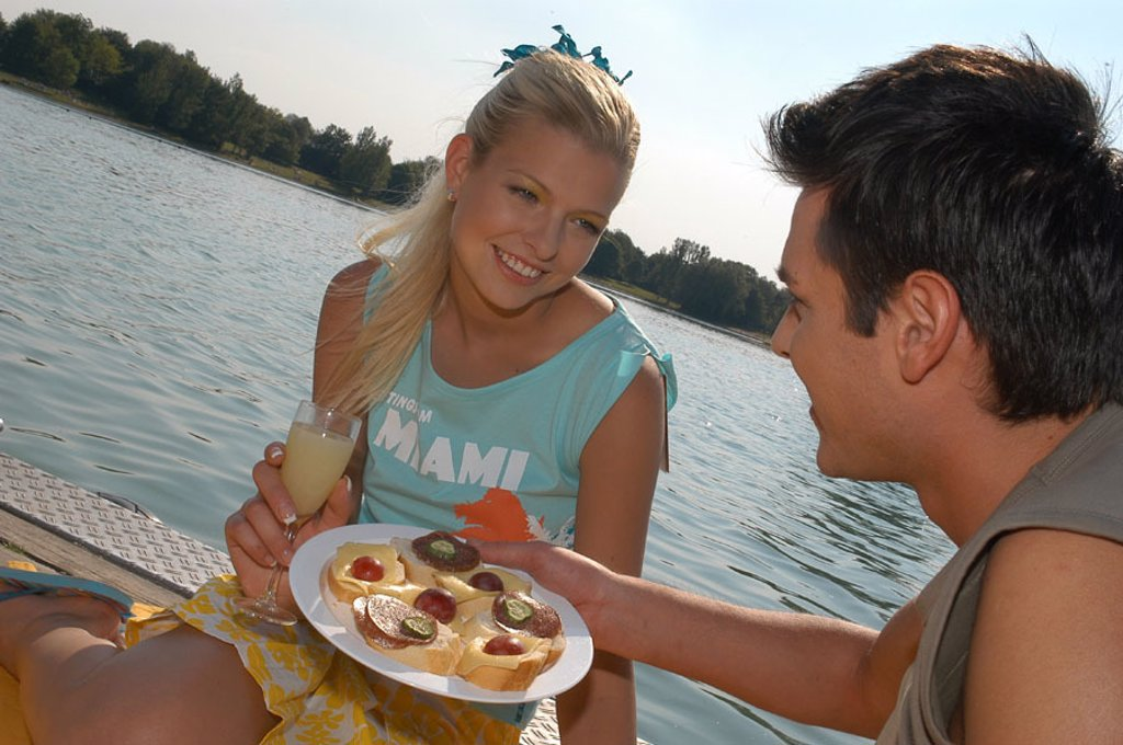 Stock Photo: 1558-89549 Sea, bridge, couple, teenagers, falls in love,  Picnic,   Teenager, youth, teenager couple, 16-18 years, partnership, relationship, love, romanticism, togetherness, surprise, Lifestyle, summer, outside, plates morsel champagne glass, smiling, smiling at,