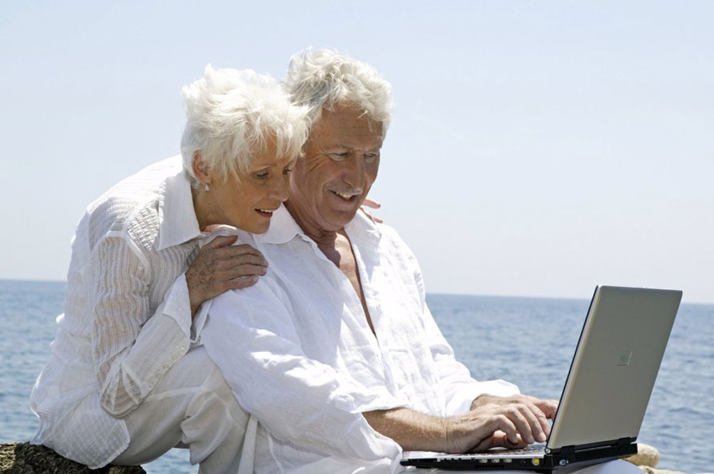 Stock Photo: 1558-89758 Sea, rock coast, senior couple, laptop,  Data input, happy,   Series, 50-60 years, well Age, seniors couple couple white-haired clothing white, sitting, computers wearable, Internetsurfen, internet, Chatten, telecommunication, data processing, balance, to
