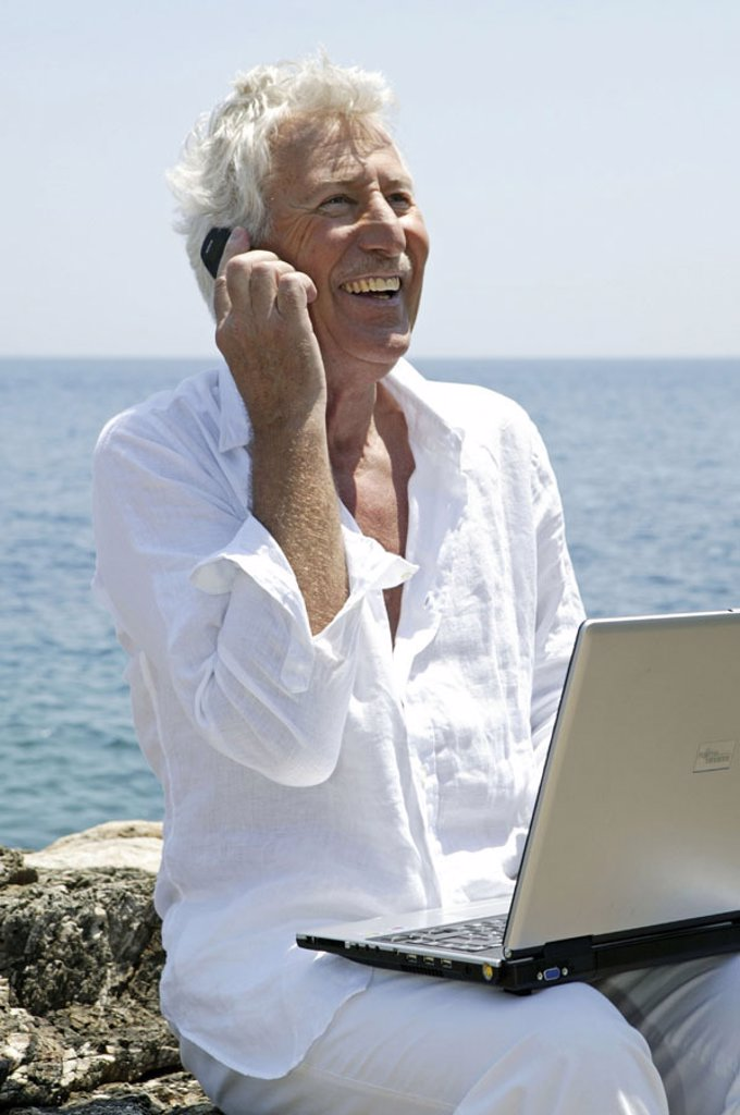 Sea, rock coast, senior, laptop,  Cell phone, telephones, happy,   Series, 50-60 years, seniors, man, white-haired, clothing white that computers, well Age, sit wearable, Internetsurfen, internet, Chatten, data processing, Workaholic, telephone, telecommu : Stock Photo
