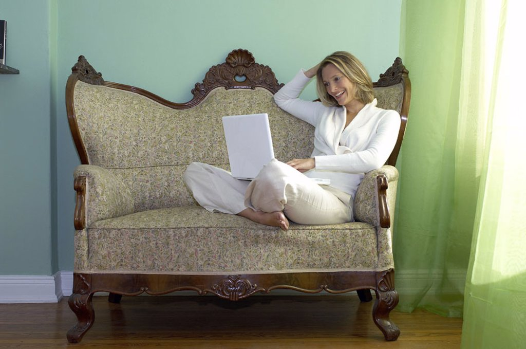 Stock Photo: 1558-90016 Sofa, woman, laptop, smiling,  Data input,   Series, young, 20-30 years, 30-40 years, single, blond, leisurewear, nakedfoot, tailor seat whole bodies leisure time, relaxen, Lifestyle, computers, wearable, data input, e-mail, writes, reading, chatten, User