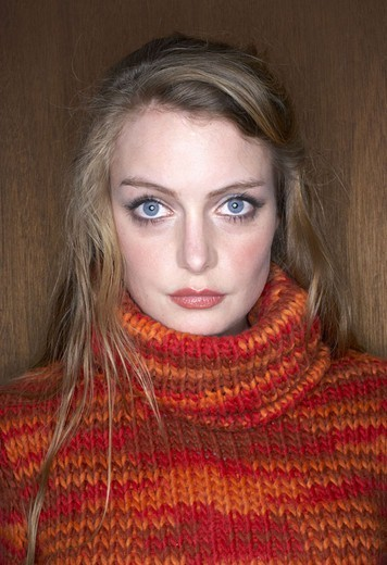 Woman, young, blond, seriously, Rollkragenpulli,  Portrait,   Women portrait, 20-30 years, long-haired, made up, eye color blue, gaze camera, rope sweater, turtlenecks, orange, background, wooden, wood wall, interior, : Stock Photo