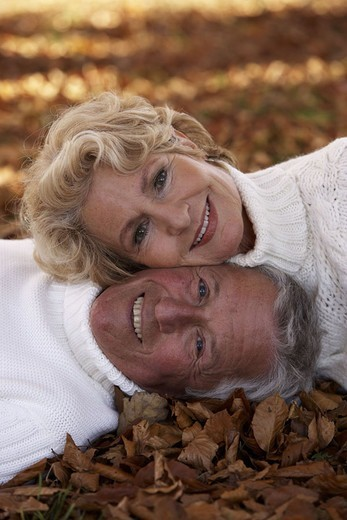 Stock Photo: 1558-90443 Senior couples, fall foliage, lie,  smiling, happily, portrait,   Seniors, 60-70 years, well Age, couple partnership couple, happily, cheerfully, foliage, abandoned, ground, one on the other, love harmony proximity, affection, mood positively, mutuality,