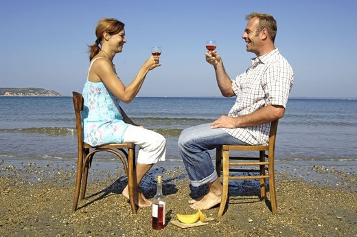Chairs smile beach, couple, gaze contact,  sitting, opposite, wine glasses, zuprosten,   Series, 30-40 years, partnership, relationship, love, togetherness, happily, flirt, vacation acquaintance, nakedfoot, enjoying, leisure time, vacation, , romanticism, : Stock Photo