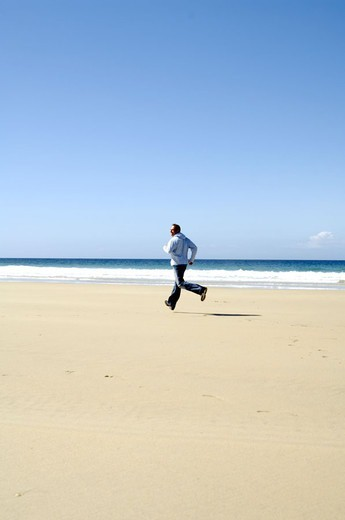 Stock Photo: 1558-90601 Beach, man, leisurewear, running,  on the side,   30-40 years, whole bodies, movement, fun, joy, recuperation, leisure time, enjoying vacation, sandy beach sea azure, cloudless Textfreiraum,