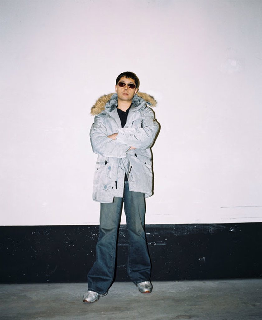 Stock Photo: 1558-90843 Panjabi MC, DJ, London, personal rights heed!  Musicians, Winterjacke,  Sun glass, indoors, April 2003,  Man, Indians, personality, music, pop, Popmusiker, artists, known, press date, photo date, shoes, jacket, silvery, glasses, wall, standing, seriously,