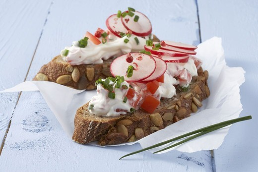 Wood table, sandwich paper, slice of breading,  Fresh cheese, vegetables,   Pumpkin seed bread, disks, bread spread, cut open milk product, tomatoes radishes chive, nutrition healthy, full value food, low-calorie, low-fat, vegetarian, breakfast, quietly l : Stock Photo