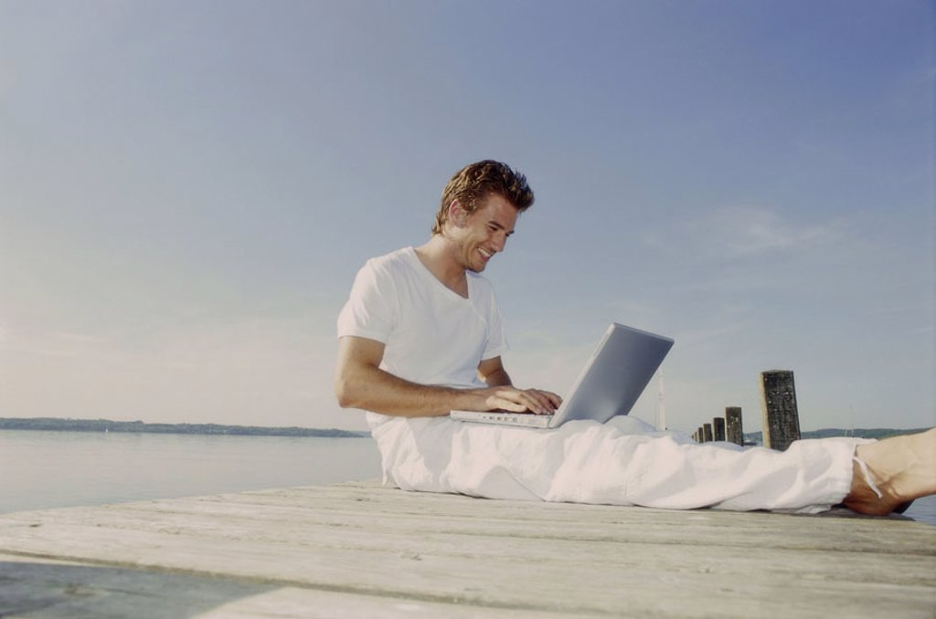 Stock Photo: 1558-92114 Bridge, man, young, sitting, laptop,  Data input,   20-30 years, leisure time, leisurewear, nakedfoot, summer, outside, sunny, boat bridge, sea, computers, flexibility, mobility, writes, taps, reading, chatten, e-mail, User, on-line, wireless, communicati
