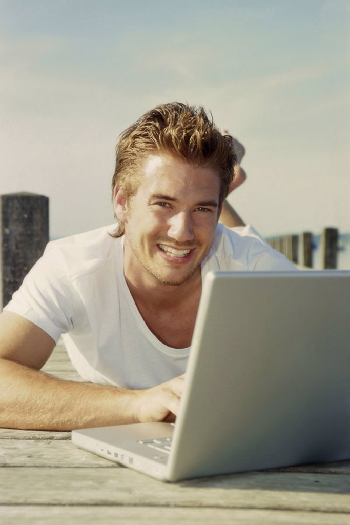 Bridge, man, young, laptop,  Data input, smiling, prone position,   20-30 years, leisure time, leisurewear, nakedfoot, summer, outside, sunny, boat bridge, computers, flexibility, mobility, writes, taps, reading, chatten, e-mail, User, on-line, wireless, : Stock Photo