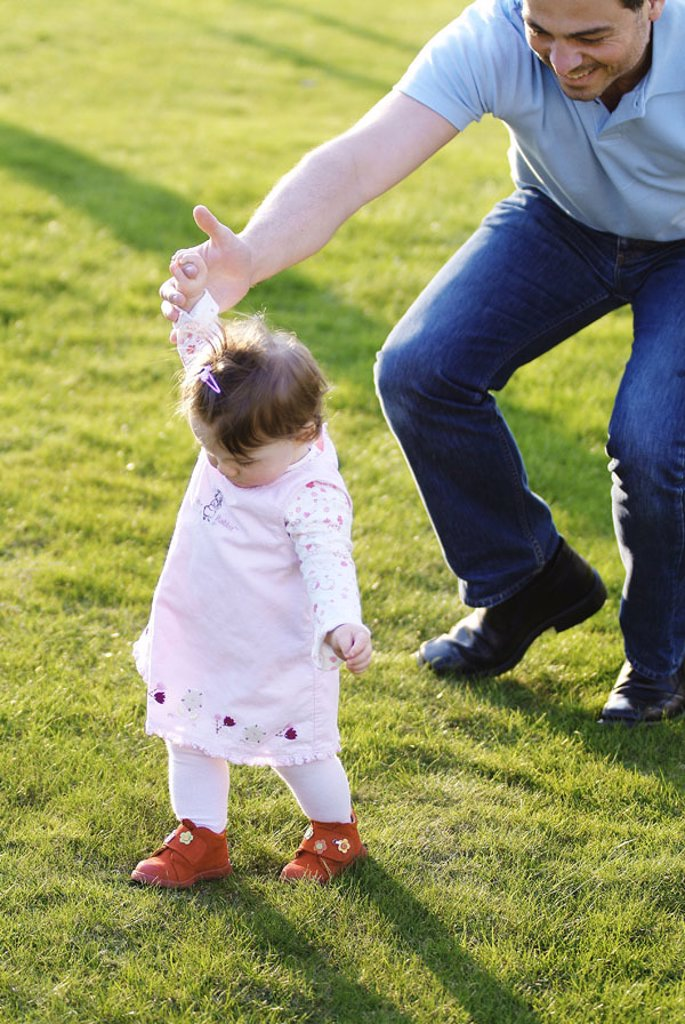 Meadow, father, daughter, hand,  holding, test run,   Man, 30-40 years, parent, child, toddler, 1-2 years, baby, experience, development, development phase, learning process, support, childhood, summer, outside, : Stock Photo