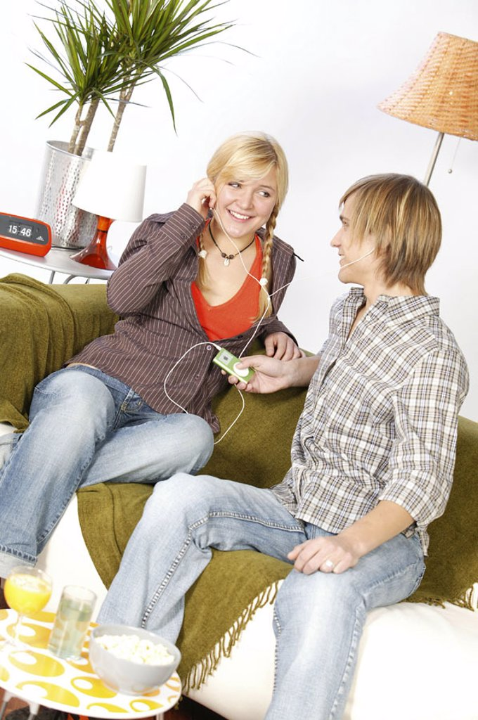Stock Photo: 1558-92832 Sofa, teenagers, couple, sitting, MP3-Player,  Headphones, music, gaze contact, hearing,   Series, youth, teenagers, teenager couple, 16-18 years, leisure time, Lifestyle, indoors, at home, living rooms, MP3, i-Pod, favorite music, listening, together, sm