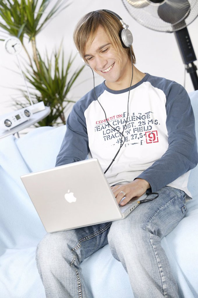 Teenager, smiling, laptop,  Data input, headphones, music hearing,  no property release,  Series, youth, teenagers, man, young, 17-19 years, leisure time, Lifestyle, computers, wearable, data input, e-mail, writes, taps, chatten, internet, Internetsurfen, : Stock Photo