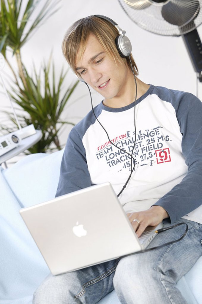 Stock Photo: 1558-92842 Teenager, smiling, laptop,  Data input, headphones, music hearing,  no property release,  Series, youth, teenagers, man, young, 17-19 years, leisure time, Lifestyle, computers, wearable, data input, e-mail, writes, taps, chatten, internet, Internetsurfen,
