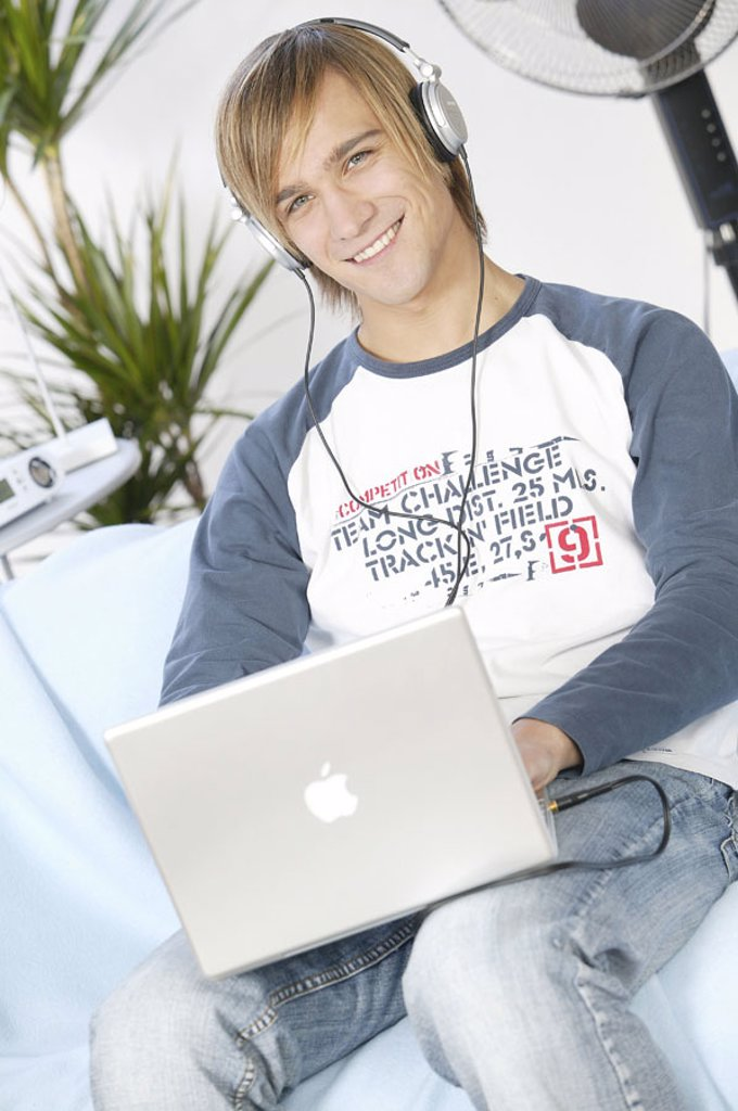 Stock Photo: 1558-92843 Teenager, smiling, laptop,  Data input, headphones, music hearing,  no property release,  Series, youth, teenagers, man, young, 17-19 years, leisure time, Lifestyle, computers, wearable, data input, e-mail, writes, taps, chatten, internet, Internetsurfen,