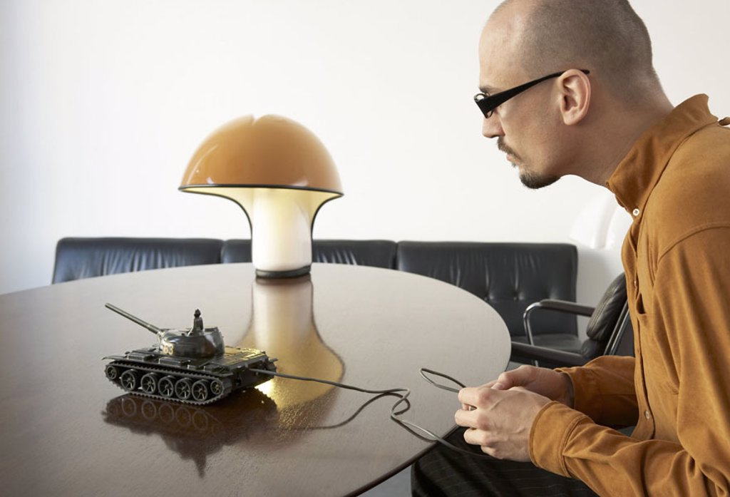 Stock Photo: 1558-94767 Sits man, table, tanks,,  , plays, profile,  broached,  20-30 years, glasses, glasses bearers, beard, Glatze, lamp, sofa, toy tanks, concentration, fascination, ´game child´, toy, remote control, war, war game, leisure time, distraction, strategy, remote