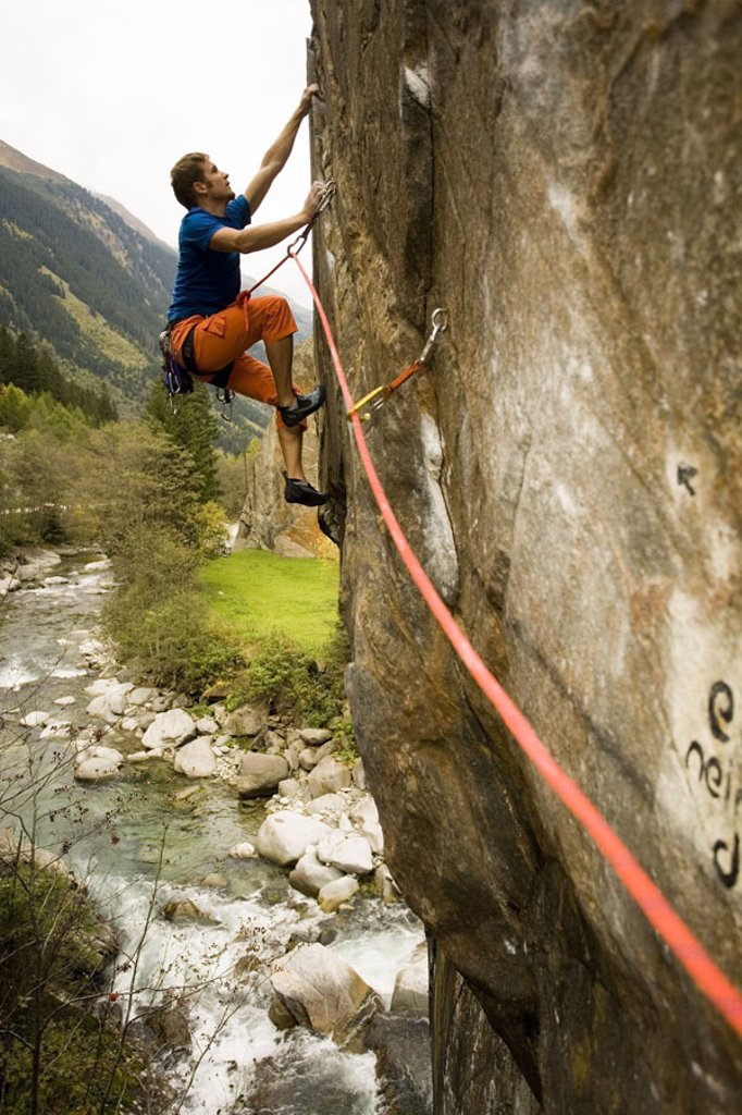 Stock Photo: 1558-95027 Rock wall, man, young, climbs,    Series, rocks, climbers, 20 years, bur out armament, rock, steep wall, vertically, roped, secured, rope, mountain rope, Kletterseil, Klettersport, sport, leisure time, hobby, activity, concept, strength, endurance, condit