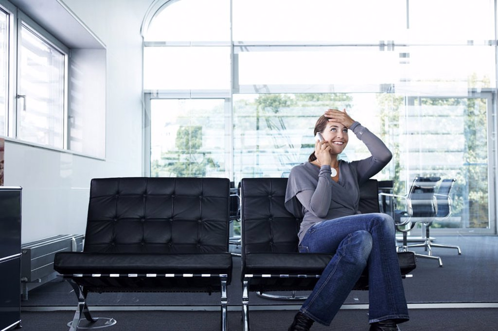 Office, leather chairs, businesswoman,  telephones, gesture, relief,   sitting series, woman, 20-30 years, employees, chairs, bench, cell phone telecommunication information consultation problem solution, laughing, pleased, ´flash of inspiration´, joy, co : Stock Photo