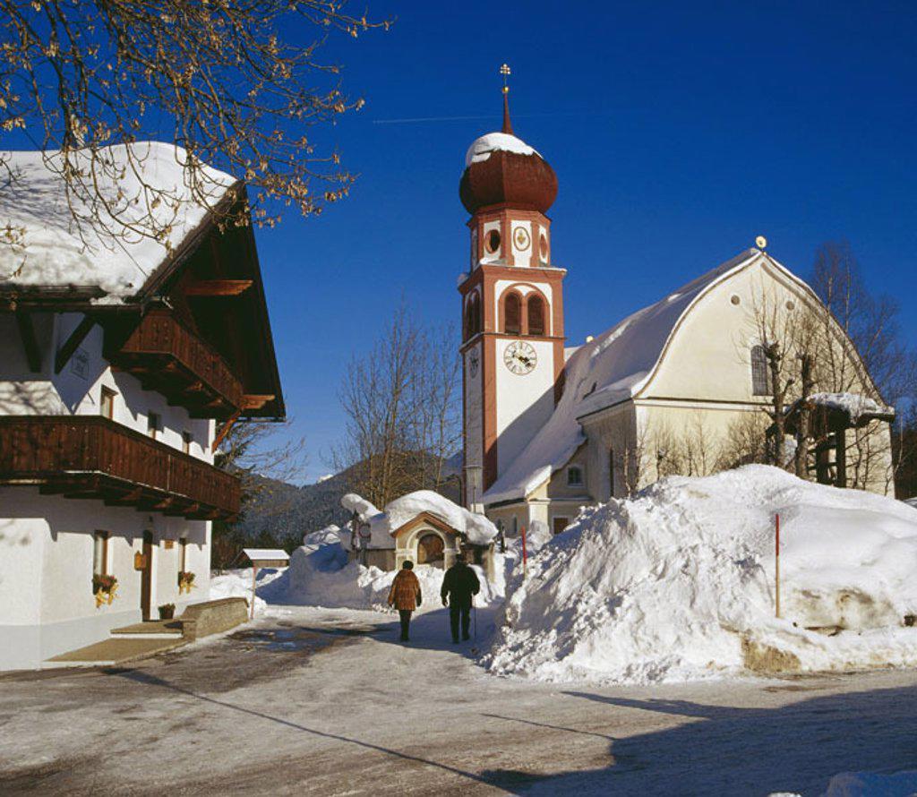 Stock Photo: 1558-98641 Austria, Tyrol, Leutasch,  Farmhouse, church, street,  Passer-bys, winters,  North Tyrol, mountain region, alpine region, tourist center, house, residence, buildings, season, fork, roadside, snow masses, snow, people, pedestrians, Oberleutasch, church ´Ma